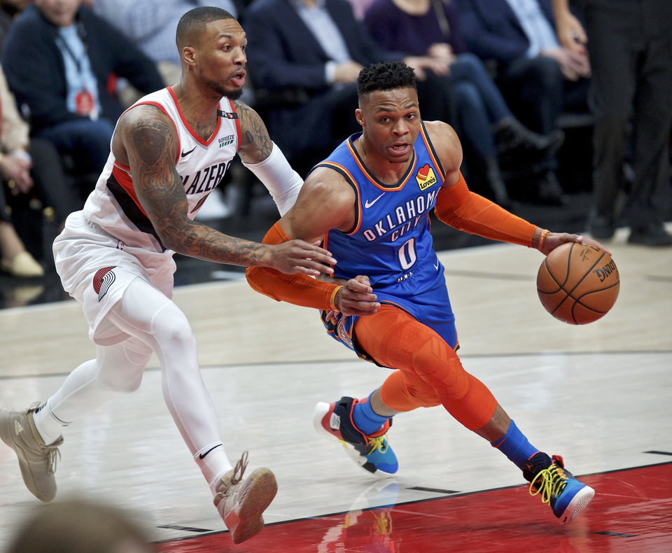 Photo - Oklahoma City Thunder guard Russell Westbrook, right, dribbles past Portland Trail Blazers guard Damian Lillard during the first half of Game 2 of an NBA basketball first-round playoff series Tuesday, April 16, 2019, in Portland, Ore. (AP Photo/Craig Mitchelldyer)