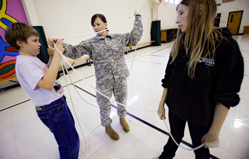 Photo - Trinity School students Zane Powell, left, and Willow Gravitt work with National Guard member Kerri Keck on a team building exercise at the school on Friday, April 24, 2009, in Oklahoma City, Okla.  Photo by Chris Landsberger, The Oklahoman