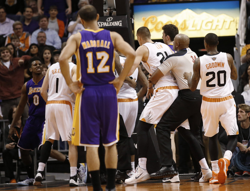 Photo - Los Angeles Lakers' Nick Young, left, has words with Phoenix Suns guard Goran Dragic (1) after Young was fouled by Suns' Alex Len during the second quarter of an NBA basketball game Wednesday, Jan. 15, 2014, in Phoenix. (AP Photo/The Arizona Republic, Michael Chow) MESA OUT  MARICOPA COUNTY OUT  NO SALES