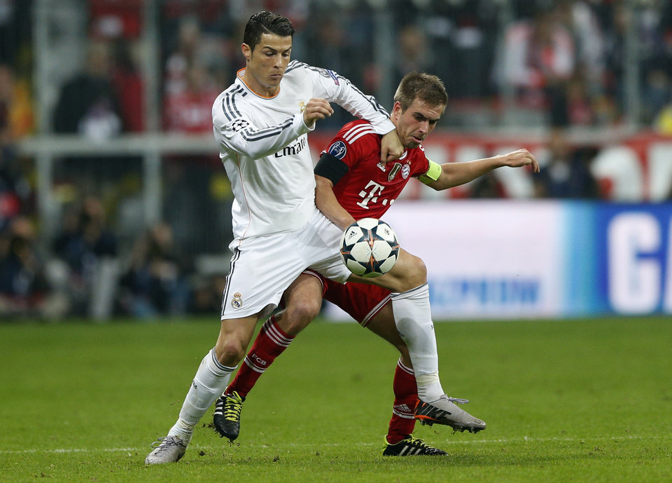 Photo - Real's Cristiano Ronaldo, left, and Bayern's Philipp Lahm challenge for the ball during the Champions League semifinal second leg soccer match between Bayern Munich and Real Madrid at the Allianz Arena in Munich, southern Germany, Tuesday, April 29, 2014. (AP Photo/Matthias Schrader)