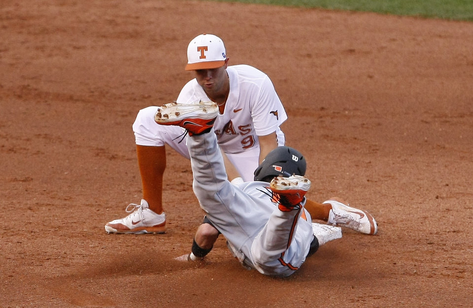 Photo - Texas short stop C.J. Hinojosa tags out Oklahoma State Aaron Cornell at second in the second inning of a second-round game in the Big 12 conference NCAA college baseball tournament in Oklahoma City, Thursday, May 22, 2014. (AP Photo/Alonzo Adams)