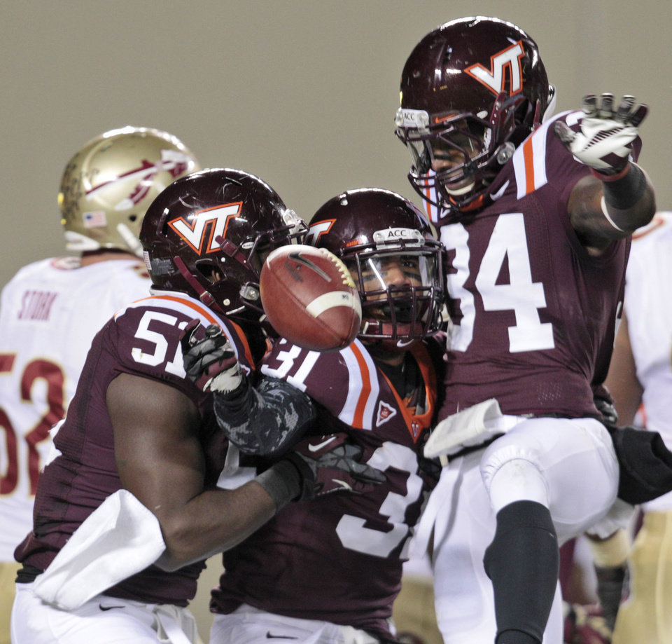 Photo -   Virginia Tech cornerback Donovan Riley (31) celebrates an interception of a Florida State pass with teammates Bruce Taylor (51) and Kyshoen Jarrett (34) during the first half of an NCAA college football game in Blacksburg, Va., Thursday, Nov. 8, 2012. (AP Photo/Steve Helber)