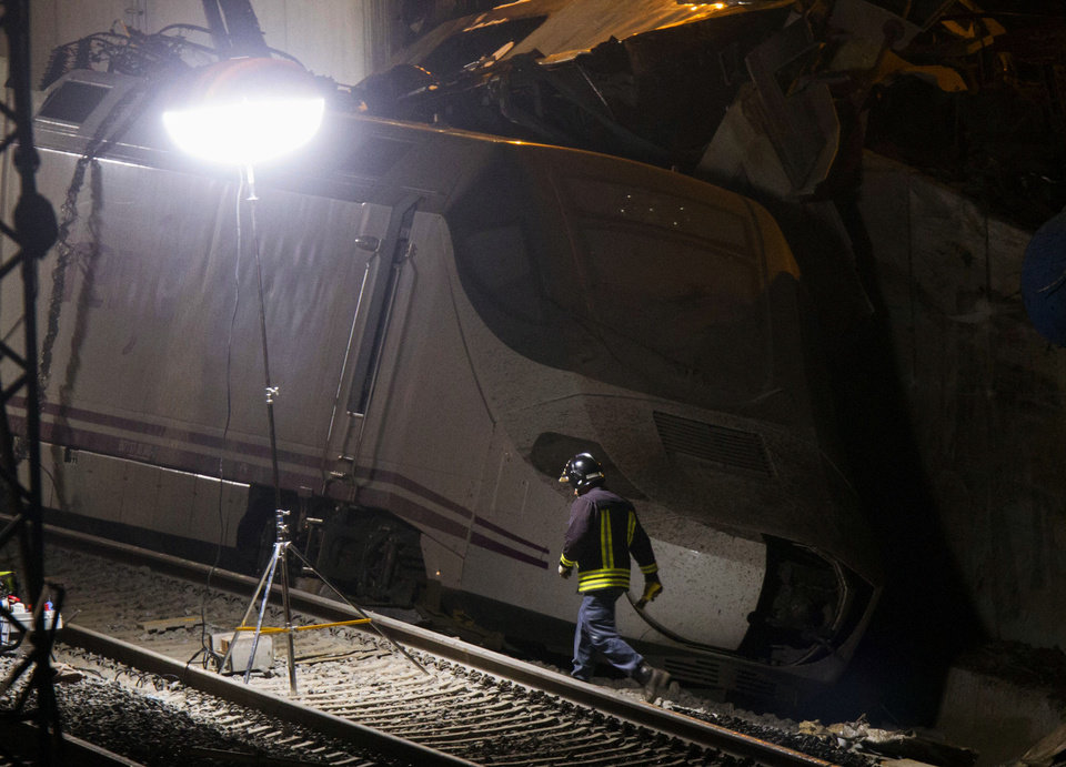 Photo - An emergency rescuer walks along an derailed train in Santiago de Compostela, Spain, on Thursday, July 25, 2013. A passenger train derailed Wednesday night on a curvy stretch of track in northwestern Spain, killing at least 40 people caught inside toppled cars and injuring at least 140 in the country's worst rail accident in decades, officials said. (AP Photo/ Lalo Villar)