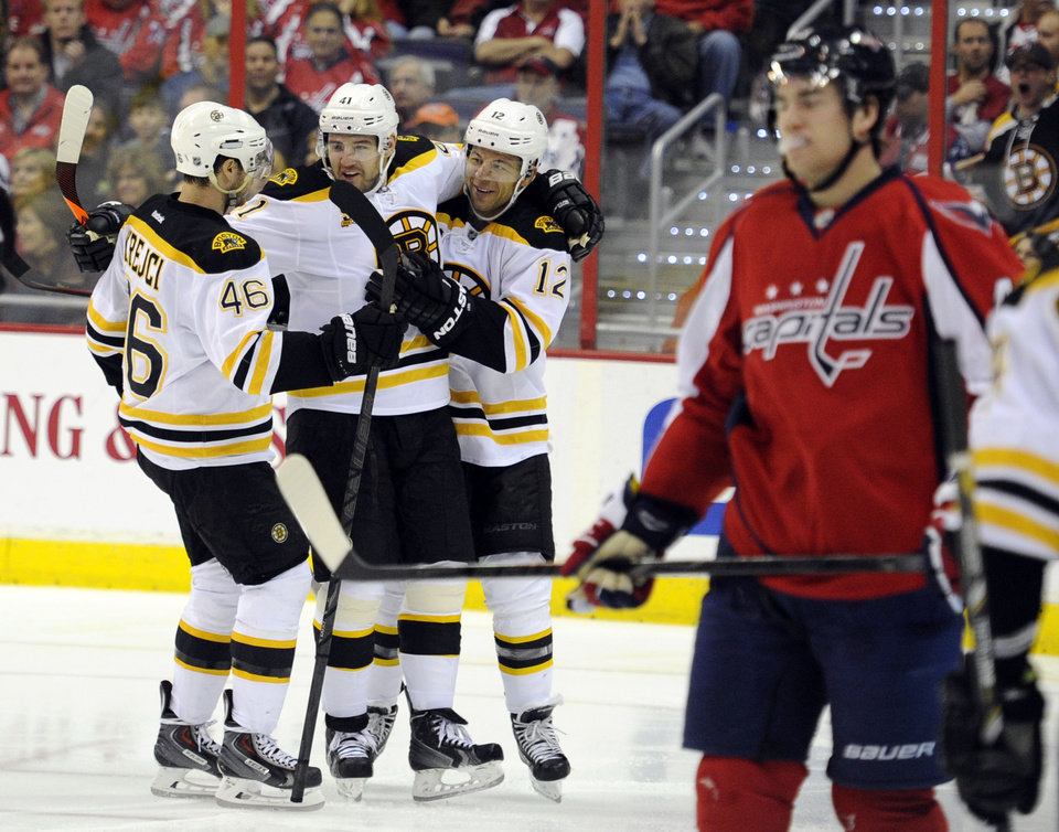 Photo - Boston Bruins right wing Jarome Iginla (12) celebrates his goal against the Washington Capitals with David Krejci (46), of the Czech Republic, and Andrej Meszaros (41) during the second period of an NHL hockey game, Saturday, March 29, 2014, in Washington. (AP Photo/Nick Wass)
