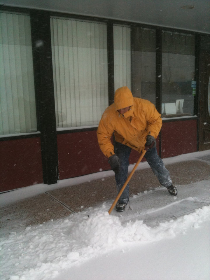 Steve Strange DDS shovels snow in front of his business Broadway Family Dentistry in Edmond