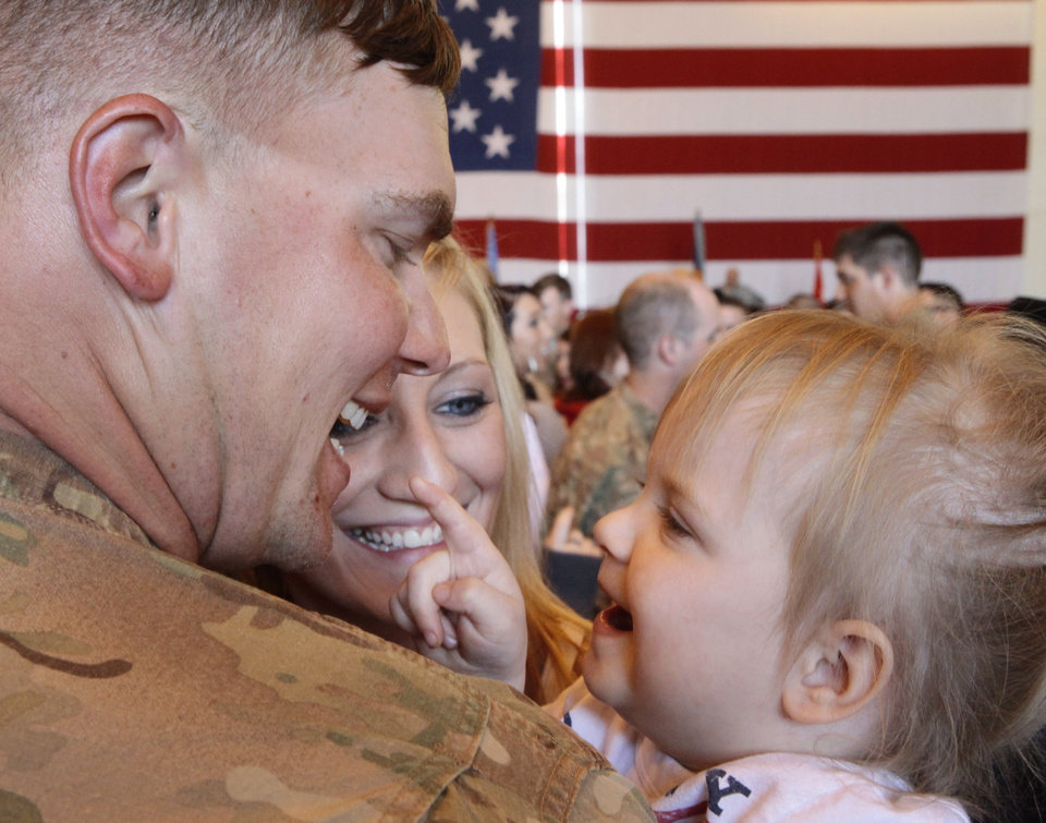 CW2 Troy Miller hugs his wife Haley and daughter Tucker, 4, during the welcome home ceremony. About 250 members of the The Oklahoma National Guard, 45th Infantry Brigade Combat Team (IBCT) returned from Afghanistan and Kuwait on Wednesday, March 28, 2012. Photo By David McDaniel/The Oklahoman