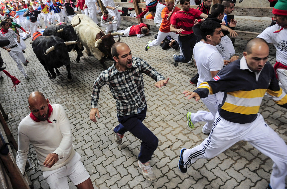 Photo - Revelers run ahead of Garcigrande fighting bulls before they enter the bull ring, during the running of the bulls,  at the San Fermin festival, in Pamplona, Spain, Thursday, July 10, 2014. Revelers from around the world arrive to Pamplona every year to take part in some of the eight days of the running of the bulls glorified by Ernest Hemingway's 1926 novel