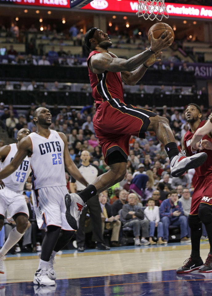 Photo - Miami Heat's LeBron James, top, drives past Charlotte Bobcats' Al Jefferson, left, during the second half of an NBA basketball game in Charlotte, N.C., Saturday, Jan. 18, 2014. The Heat won 104-96 in overtime. (AP Photo/Chuck Burton)