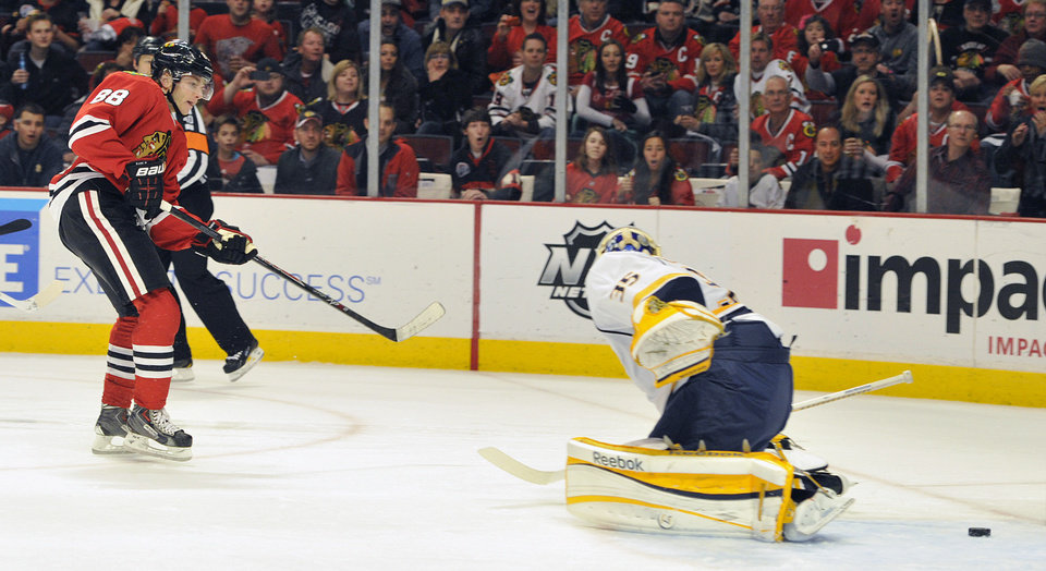 Photo - Chicago Blackhawks' Patrick Kane (88) shoots the puck past the Nashville Predators' Pekka Rinne during the second period of an NHL hockey game on Friday, April 19, 2013, in Chicago. (AP Photo/Jim Prisching)