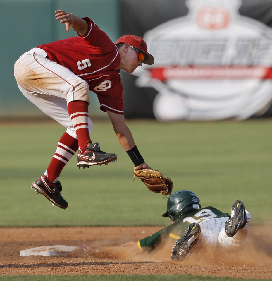 Photo - OU's Caleb Bushyhead (5) leaps while tagging out Baylor's Logan Vick (19) in the seventh inning during a Big 12 Baseball Championship tournament game between the Oklahoma Sooners and Baylor Bears at the Chickasaw Bricktown Ballpark in Oklahoma City,Thursday, May 24, 2012. OU won, 3-2. Photo by Nate Billings, The Oklahoman