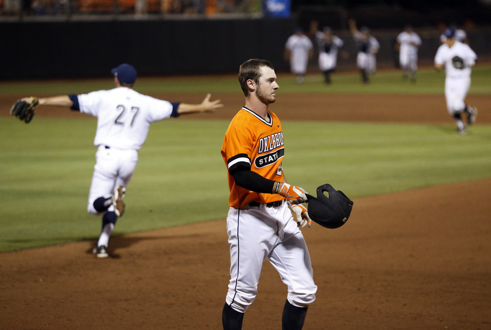 Photo - UC Irvine celebrates as OSU's Conor Costello (24), the Cowboys' last out, removes his helmet at the end of Game 2 of the NCAA baseball Stillwater Super Regional between Oklahoma State and UC Irvine at Allie P. Reynolds Stadium in Stillwater, Okla., Saturday, June 7, 2014. UC Irvine won 1-0. Photo by Nate Billings, The Oklahoman