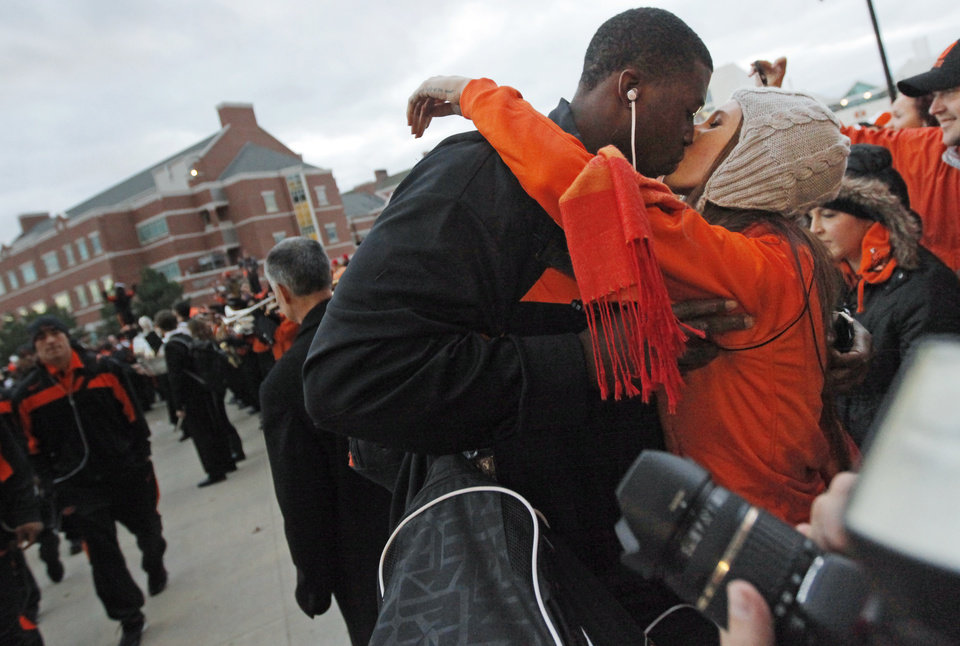 Photo - OSU player Davidell Collins (98) kisses his girlfriend, Nikki Gunter, an OSU student from Mustang, Okla., during the Spirit Wak before the Bedlam college football game between the Oklahoma State University Cowboys (OSU) and the University of Oklahoma Sooners (OU) at Boone Pickens Stadium in Stillwater, Okla., Saturday, Dec. 3, 2011. Photo by Nate Billings, The Oklahoman
