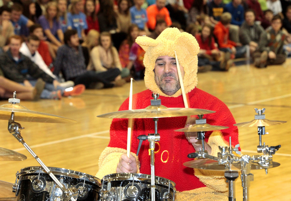 Principal Jason Pittenger plays the drums in a Winnie the Pooh costume during the BALTO assembly on Friday at Edmond North High School.