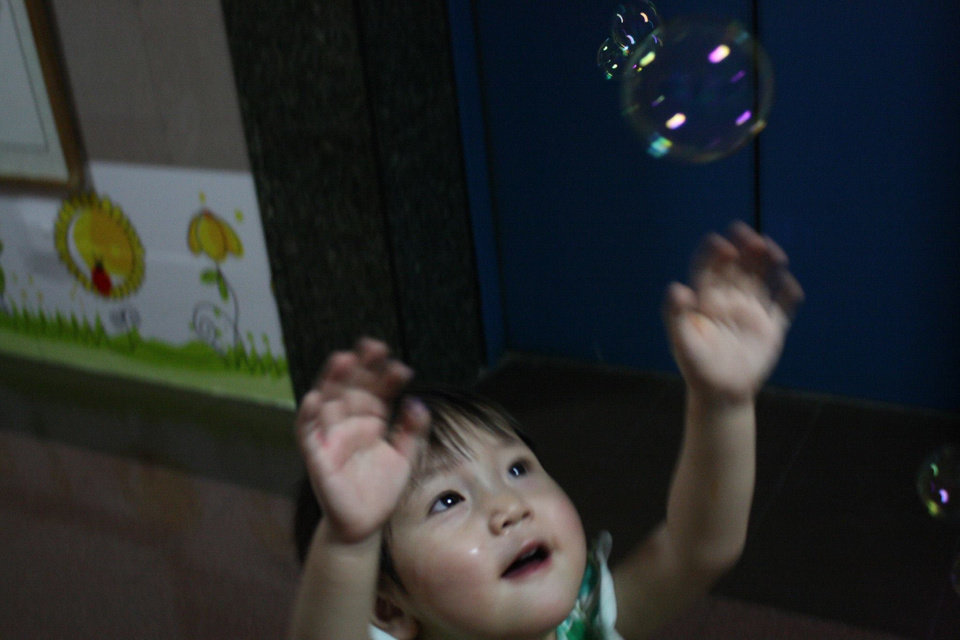 "Photo -  A child at the China Care Home in Beijing chases bubbles during a visit by Abigale ""Abbey"" White, a Deer Creek High School student, and other teens on a trip to China sponsored by Half the Sky Foundation in partnership with China's Children International. Photo provided"