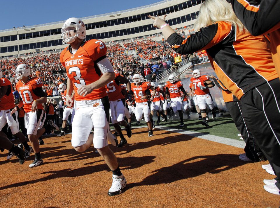 Photo - Brandon Weeden (3) and the OSU Cowboys run on the field before the college football game between the Oklahoma State University Cowboys (OSU) and the Baylor University Bears at Boone Pickens Stadium in Stillwater, Okla., Saturday, Nov. 6, 2010. Photo by Nate Billings, The Oklahoman