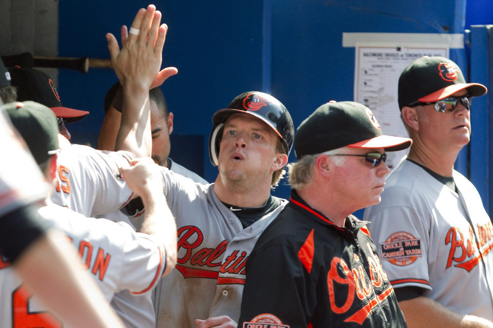 Photo -   Baltimore Orioles' Nate McLouth celebrates after scoring following a single from J.J. Hardy against the Toronto Blue Jays during the eighth inning of a baseball game, Monday Sept. 3, 2012, in Toronto. The Orioles won 4-0. (AP Photo/The Canadian Press, Chris Young)