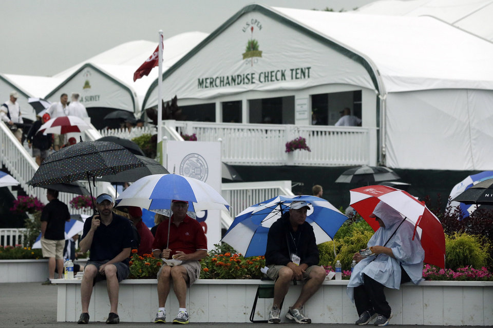 Photo - Spectators wait out a weather delay during the first round of the U.S. Open golf tournament at Merion Golf Club, Thursday, June 13, 2013, in Ardmore, Pa. (AP Photo/Gene J. Puskar)