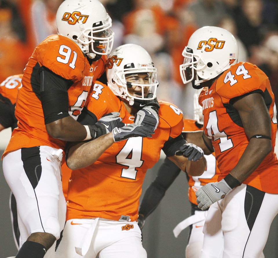 OSU's Ugo Chinasa (from left), Patrick Lavine and Donald Booker celebrate an interception returned for a touchdown by Lavine in the fourth quarter Saturday at Boone Pickens Stadium. Photo by Nate Billings, The Oklahoman