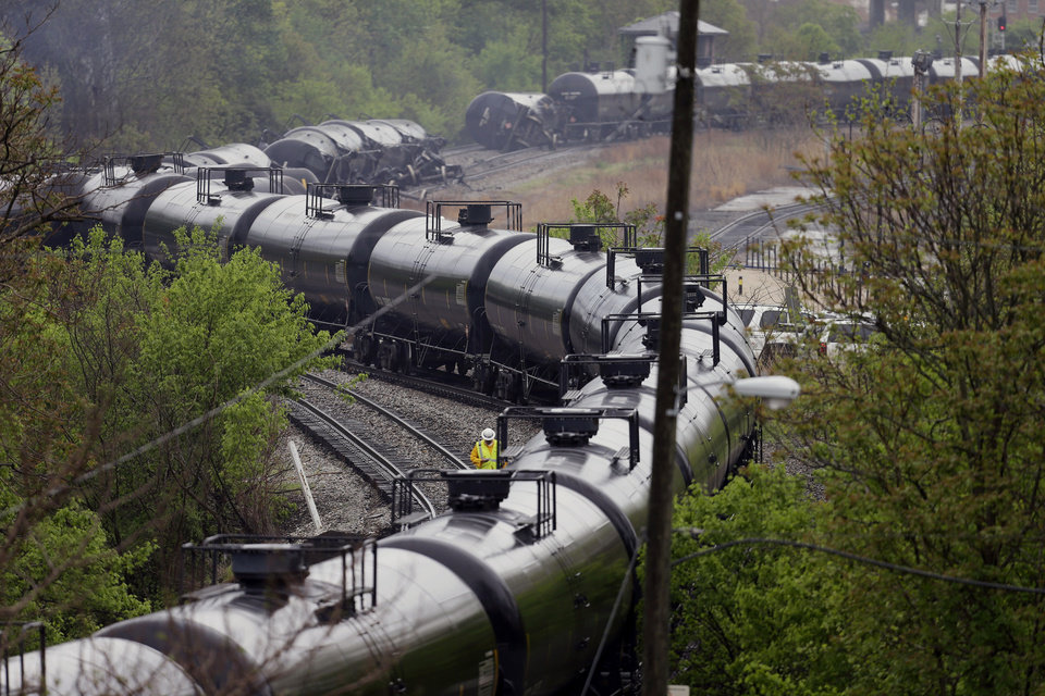 Photo - Firefighters and rescue workers work along the tracks where several CSX tanker cars carrying crude oil derailed and caught fire along the James river near downtown in Lynchburg, Va., Wednesday, April 30, 2014. Nearby buildings were evacuated for a time, but officials said there were no injuries and the city on its website and Twitter said firefighters on the scene made the decision to let the fire burn out. (AP Photo/Steve Helber)