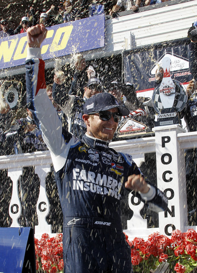 Photo - Kasey Kahne celebrates in victory lane after winning a NASCAR Sprint Cup Series auto race, Sunday Aug. 4, 2013, at Pocono Raceway in Long Pond, Pa. Jeff Gordon was second. (AP Russ Hamilton Sr.)