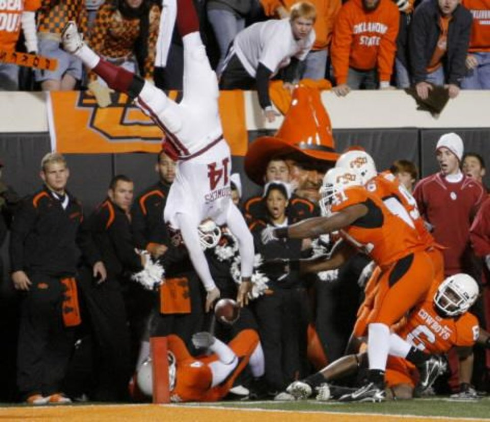 Sam  Bradford leaps over Orie Lemon during the second half of the college football game between the University of Oklahoma Sooners (OU) and Oklahoma State University Cowboys (OSU) at Boone Pickens Stadium on Saturday, Nov. 29, 2008, in Stillwater, Okla. STAFF PHOTO BY CHRIS LANDSBERGER