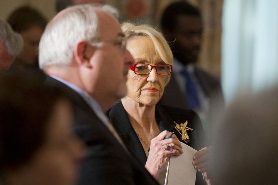 Photo - Arizona Gov. Jan Brewer waits for the arrival of President Barack Obama to speak to members of the National Governors Association in the State Dining Room of the White House in Washington, Monday, Feb. 24, 2014. (AP Photo/Jacquelyn Martin)