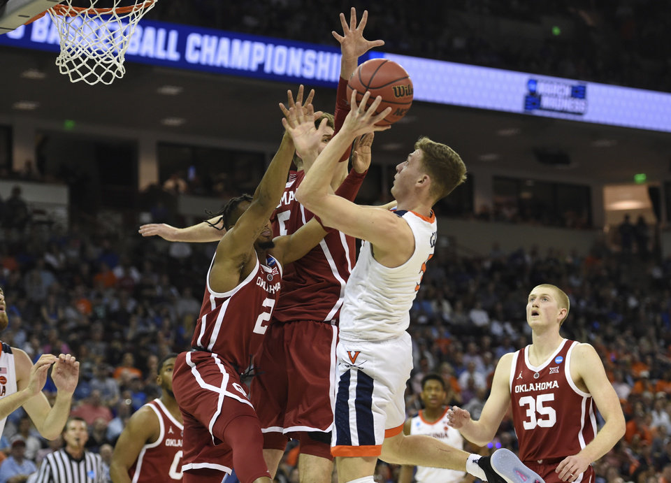 Photo - Virginia's Kyle Guy (5) shoots while defended by Oklahoma's Aaron Calixte (2) and Matt Freeman (5) during the second half of a second round men's college basketball game in the NCAA Tournament in Columbia, S.C. Sunday, March 24, 2019. (AP Photo/Richard Shiro)