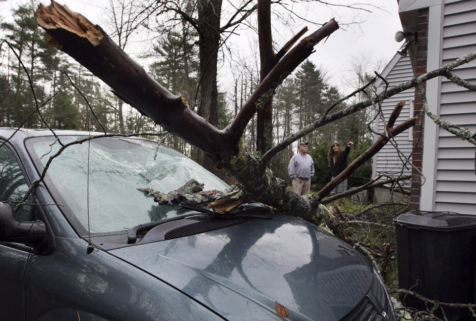 Bill Hughes and Priscilla Martell examine damage, Tuesday, Oct. 30, 2012, after a tree limb smashed the windshield of a van and punctured the roof of the Deering Road group home during superstorm Sandy in Gorham, Maine. Sandy made landfall Monday, caused multiple fatalities, halted mass transit and cut power to more than 6 million homes and businesses. (AP Photo/Robert F. Bukaty) ORG XMIT: MERB101