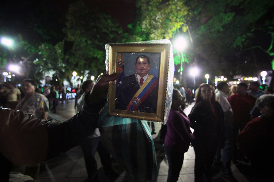 Photo - A man holds up an image of Venezuela's President Hugo Chavez as people gather to pray for him at Simon Bolivar square in Caracas, Venezuela, Tuesday, Dec. 11, 2012. Doctors began operating on Chavez  in Cuba, his government said, after his cancer reappeared despite a year and a half of surgeries and treatments. (AP Photo/Fernando Llano)