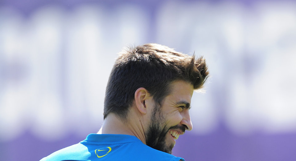 Photo - FC Barcelona's Gerard Pique smiles during a training session,  in San Joan Despi, Spain, Friday, May 16, 2014. Barcelona faces Spanish leader Atletico Madrid in a winner-takes-all league finale on Saturday, when the defending champion could yet lift its fifth title in six seasons. (AP Photo/Manu Fernandez)