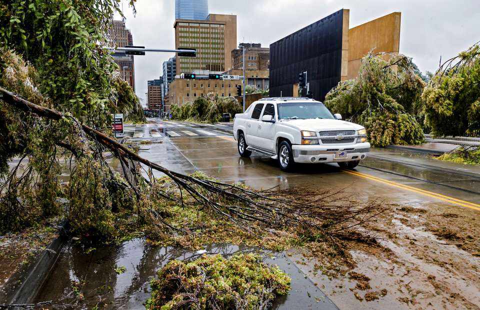 Photo - A car drive along Robinson Ave. avoiding the debris from broken trees that litter the road in Oklahoma City, Okla. on Tuesday, Oct. 27, 2020, after a winter blast hit the state.  [Chris Landsberger/The Oklahoman]