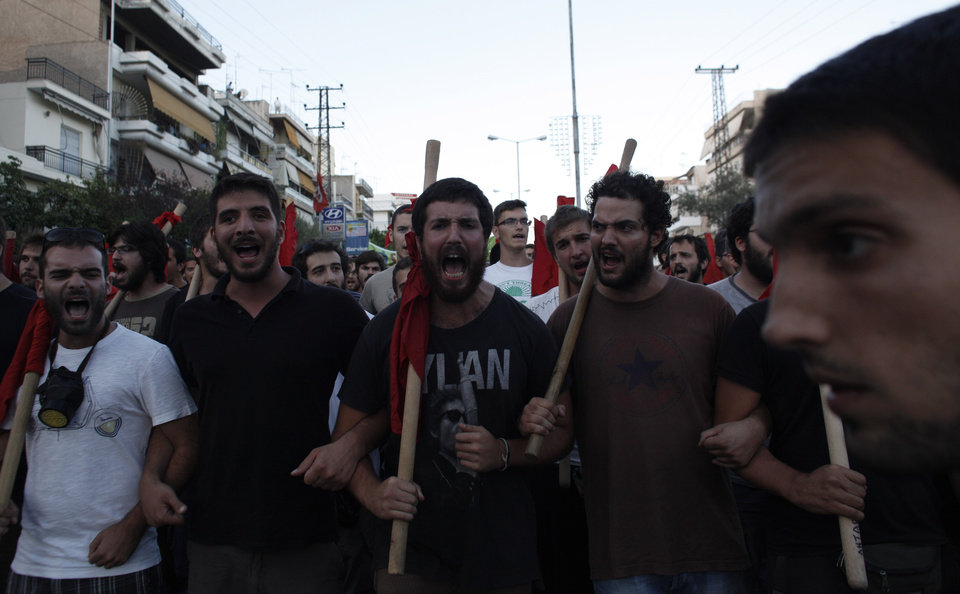 Photo - Protesters shout slogans during a protest after the stabbing of a 34 year old man in the suburb of Keratsini near Athens , Wednesday, Sept. 18,  2013. Violent clashes broke out Wednesday in several Greek cities after a member of the country's far-right Golden Dawn party was arrested in the fatal stabbing of a 34-year-old musician described as an anti-fascist activist. The stabbing drew condemnation from across Greece's political spectrum and from abroad. While the extremist Golden Dawn has been blamed for numerous violent attacks in the past, the overnight stabbing is the most serious violence directly attributed to a member so far. (AP Photo/Kostas Tsironis)