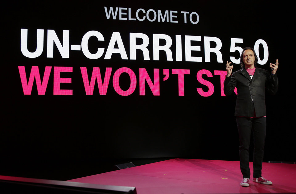 Photo - T-Mobile CEO John Legere speaks at T-Mobile's Uncarrier 5.0 event, Wednesday, June 18, 2014, in Seattle. (AP Photo/Ted S. Warren)