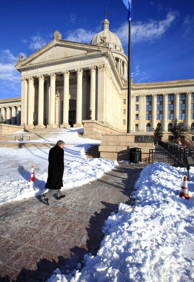 Photo - Commerce secretary Dave Lopez walking the path shoveled between snow drifts to the south entrance of the state Capitol in Oklahoma City Thursday, Feb. 3, 2011. Photo by Paul B. Southerland, The Oklahoman
