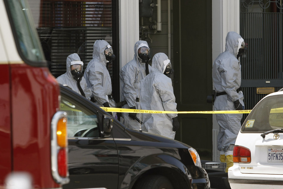 Photo - In this photo taken May 31, 2014, agents in hazardous material suits are seen as the FBI searches a building in San Francisco. A San Francisco social media maven and former political consultant who was wanted on suspicion of possessing explosives has been taken into custody after a three-day manhunt. Federal agents and the San Francisco police said they captured Ryan Kelly Chamberlain II, 42, on Monday, June 2, shortly after announcing that they had found his car near Crissy Field, just south of the Golden Gate Bridge. (AP Photo/San Francisco Chronicle, Michael Short) ORTHERN CALIFORNIA OUT; MANDATORY CREDIT PHOTOG & CHRONICLE; MAGS OUT; NO SALES