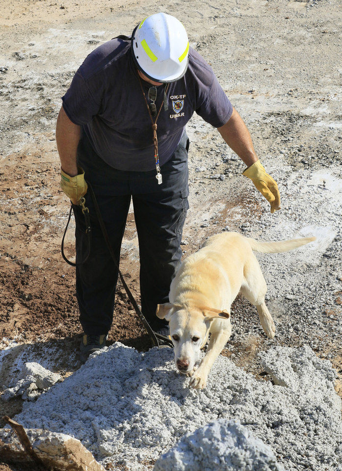 Photo -  Oklahoma City Fire Department Lt. Jason Smith releases rescue dog Jagger on Aug. 3 at the Schwarz Ready Mix rubble pile on W Reno in Oklahoma City to find a