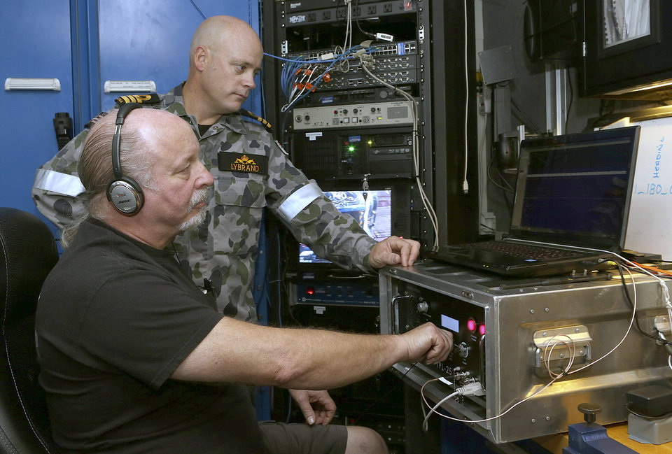 Photo - In this April 5, 2014, photo provided by the Australian Defense Force, Commander James Lybrand, left, watches as Mike Unzicker from Phoenix International monitors the feed from the towed pinger locator behind the Royal Australian Navy ship Ocean Shield in the southern Indian Ocean. Ocean Shield, which is carrying high-tech sound detectors from the U.S. Navy, is investigating a sound it picked up. (AP Photo/Australian Defense Force, Bradley Darvill) EDITORIAL USE ONLY