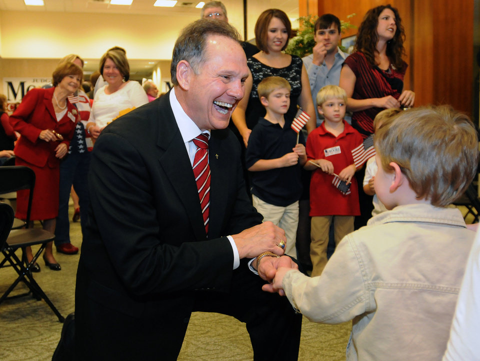 Roy Moore, candidate for Alabama Supreme Court chief justice, greets Adam DuPre', 3, of Pike Road, Ala., at his election party in Montgomery, Ala., on election night Tuesday, Nov. 6, 2012. (AP Photo/David Bundy)