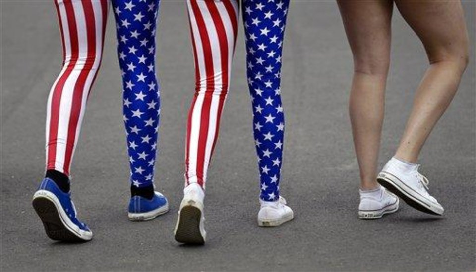 Photo - In this Thursday, Aug. 2, 2012 photo, Nick Miller, left, and his sister Kendall Miller, center, from San Francisco, wear leotards in the colors of the United States national flag as they walk with a friend through Olympic Park at the 2012 Summer Olympics, in London. Patriotism and the games have always gone together, but gone are the days when one just waved a flag. Now flags are worn, seen all over London and especially at Olympic Park and other spots where the games are being played. (AP Photo/Ben Curtis)