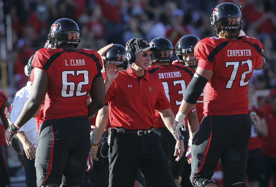 Texas Tech head coach Tommy Tuberville greets Le'Raven Clark (62) and Beau Carpenter (72) during their NCAA college football game against West Virginia in Lubbock, Texas, Saturday, Oct. 13, 2012. (AP Photo/Lubbock Avalanche-Journal, Stephen Spillman) LOCAL TV OUT ORG XMIT: TXLUB121