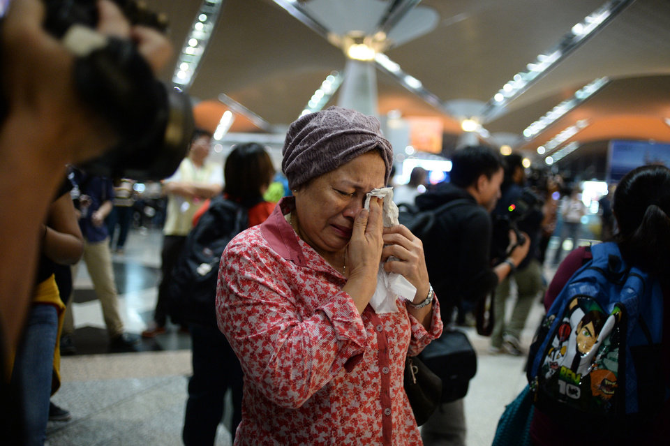 Photo - A woman reacts to news regarding a Malaysia Airlines plane that crashed in eastern Ukraine at Kuala Lumpur International Airport in Sepang, Malaysia, Friday, July 18, 2014.  Malaysia Airlines said it lost contact with Flight 17 over Ukrainian airspace Thursday. It was flying from Amsterdam to Kuala Lumpur, Malaysia. (AP Photo/Joshua Paul)