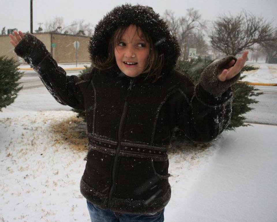 Photo - Lakyn Kennelly, 9, plays in the snow on Dec. 19, 2011, in Guymon, Okla. The heavy snow began after school let out, and officals canceled school for Tuesday, giving kids an extra day off for the Christmas holiday. A blizzard is affecting the region with heavy snow and high winds, canceling numerous local events. (AP photo/The Guymon Daily Herald, Shawn Yorks)  SHAWN YORKS - AP