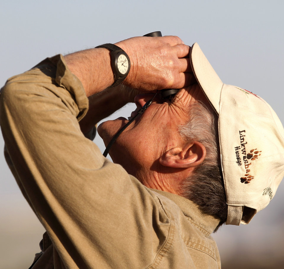 Bud Crawford, a son of Warren Crawford, uses binoculars to watch the aircraft crying his dad and brother to the proper altitude where the two can perform their skydive. Bud Crawford went up on the next flight. Warren Crawford, Oklahoma City, a 91 year-old WWII veteran, made his first skydive Saturday afternoon, Nov. 17, 2012, at Cushing Regional Airport. Crawford served as a bombardier during the war, but had never parachuted from a plane. He said this has been a dream of his for most of his life, but had promised his wife he wouldn\'t do it until after she died. Crawford\'s two sons, Steve and Bud, joined their father on the skydiving adventure.The elder Crawford performed a tandem jump with Andy Beck, an instructor at Skydive Oklahoma, which gives lessons and provides an airplane service for skydiving enthusiasts. Photo by Jim Beckel, The Oklahoman