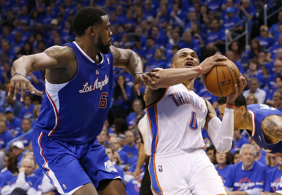 Photo - Oklahoma City Thunder guard Russell Westbrook (0) is fouled by Los Angeles Clippers center DeAndre Jordan (6) in the third quarter of Game 1 of the Western Conference semifinal NBA basketball playoff series in Oklahoma City, Monday, May 5, 2014. Los Angeles won 122-105. (AP Photo/Sue Ogrocki)