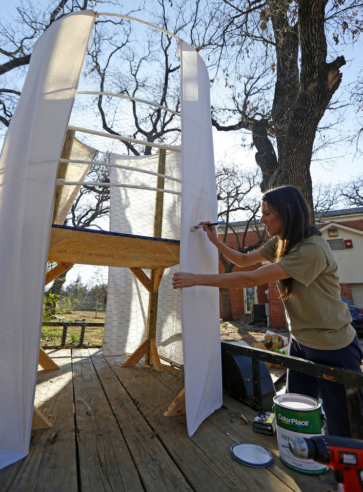 Photo - Jennifer Teel paints the Forever After Parties float for the St. Patrick's Day parade.