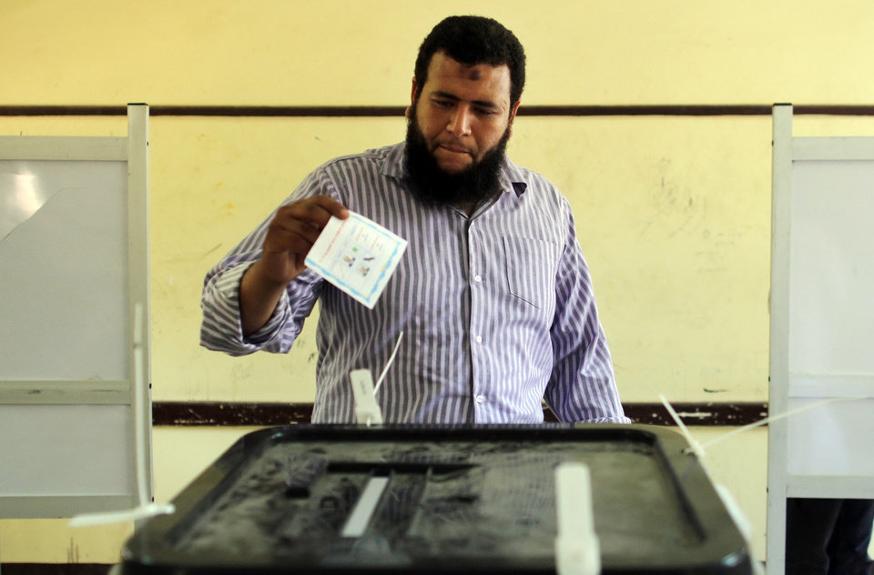 Photo - An Egyptian man casts his ballot in the presidential election in Malawi, south of Cairo, Egypt, Monday, May 26, 2014. Egyptians are choosing a new president on Monday in an election likely to be won by the man who nearly a year ago ousted the nation's first freely elected president, the Islamist Mohammed Morsi.(Ap Photo/Riger Anis, El Shorouk) EGYPT OUT