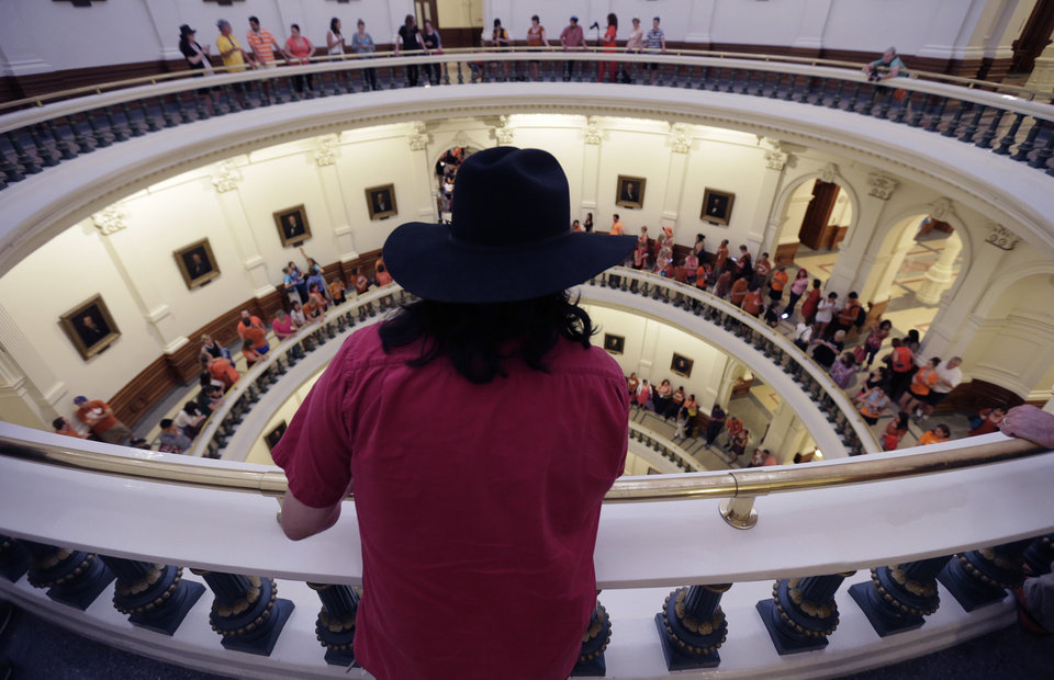 Photo - Hundreds line up to enter the Senate Chamber spills into multiple levels of the rotunda as Sen. Wendy Davis, D-Fort Worth, filibusters in an effort to kill an abortion bill, Tuesday, June 25, 2013, in Austin, Texas. The bill would ban abortion after 20 weeks of pregnancy and force many clinics that perform the procedure to upgrade their facilities and be classified as ambulatory surgical centers. (AP Photo/Eric Gay)