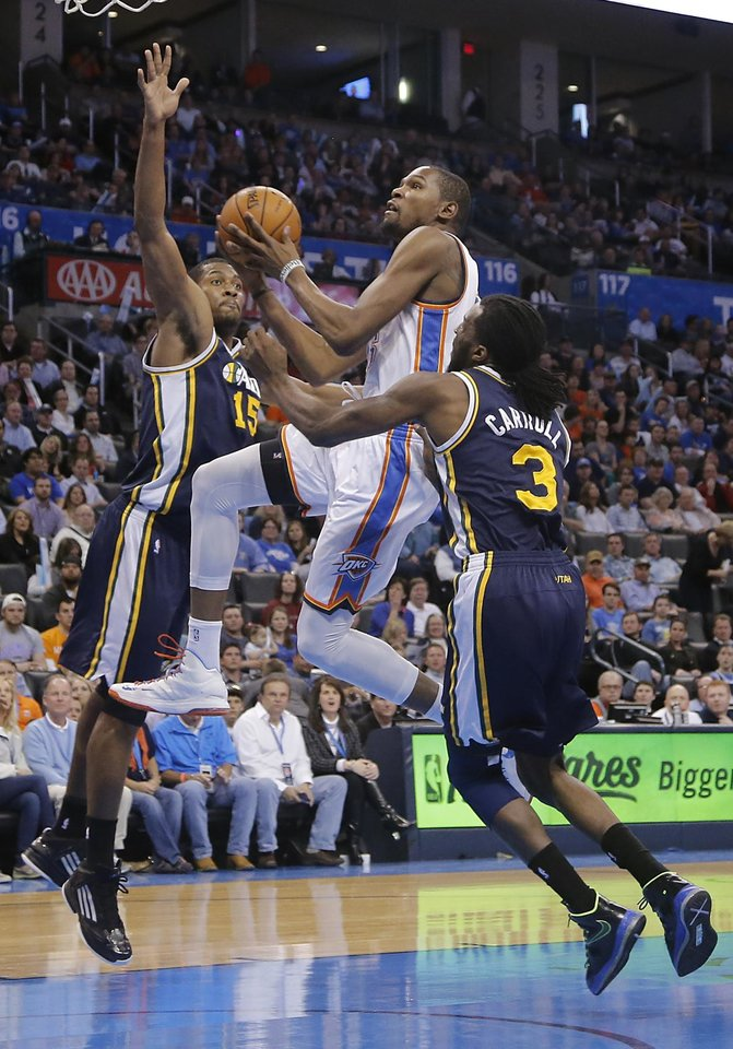 Photo - Oklahoma City Thunder's Kevin Durant (35) drive between Utah Jazz's Derrick Favors (15) and DeMarre Carroll (3) during the NBA basketball game between the Oklahoma City Thunder and the Utah Jazz at Chesapeake Energy Arena on Wednesday, March 13, 2013, in Oklahoma City, Okla. Photo by Chris Landsberger, The Oklahoman
