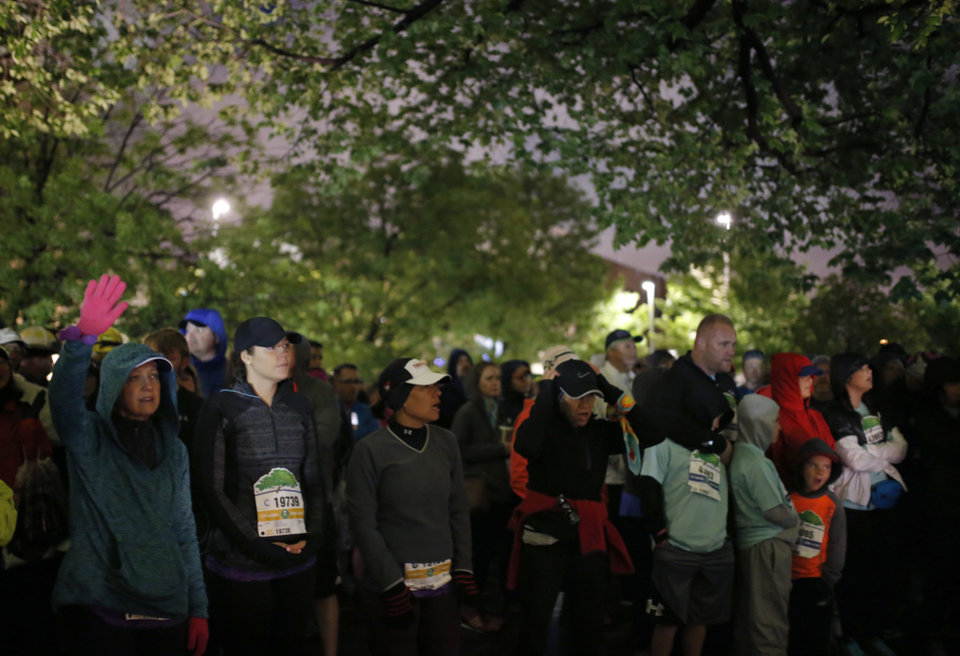 Photo - People worship at the Survivor Tree during the Sunrise Service before the 2017 Oklahoma City Memorial Marathon Sunday, April 30, 2017.  Photo by Sarah Phipps, The Oklahoman