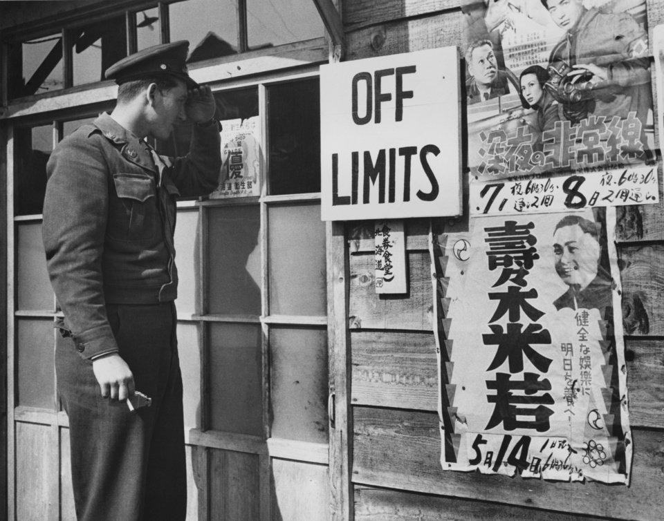 Photo - Now you have reached Chitose, near Camp Monte Stron (No.8) and here's another inquisitive Thunderbird.  He's Pvt. William R. Short, Memphis, Tenn., who wonders why this house is off limits to American troops.  The posters nailed to the wall advertise movie, but this establishment happens to be a Japanese beer hall.  Photo by  Ron Pyer.  Original date unknown.  Published in The Daily Oklahoman 06/10/1951.